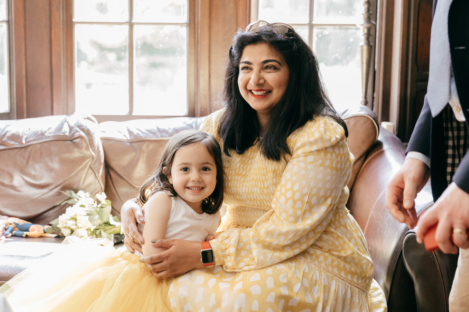 relaxed wedding photo of mother and flower girl cuddling up on sofa