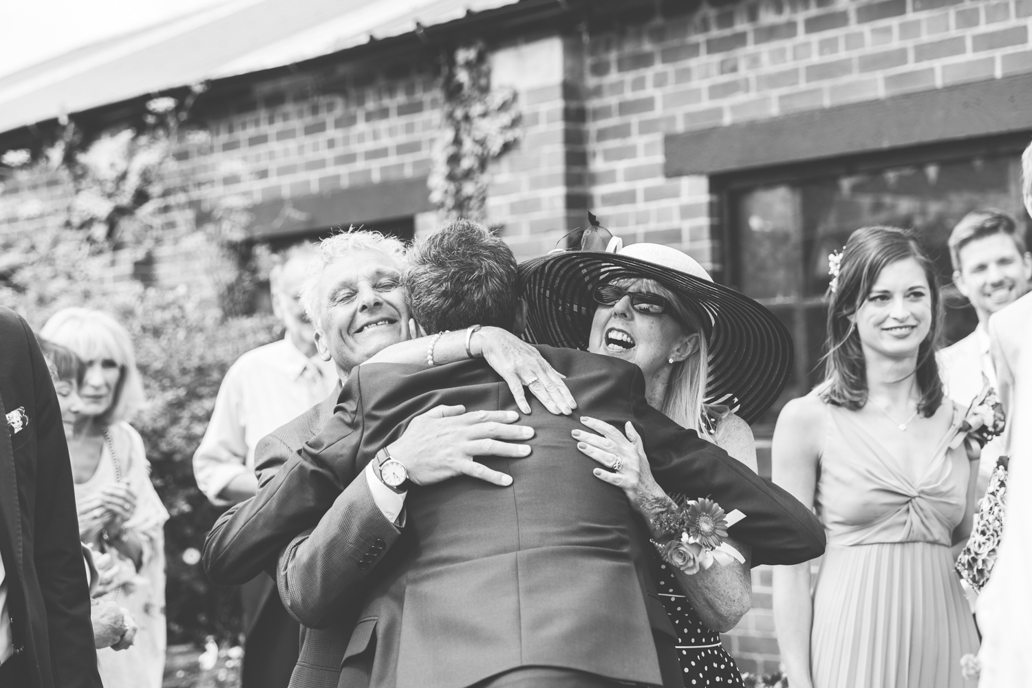candid wedding photography of parents hugging groom