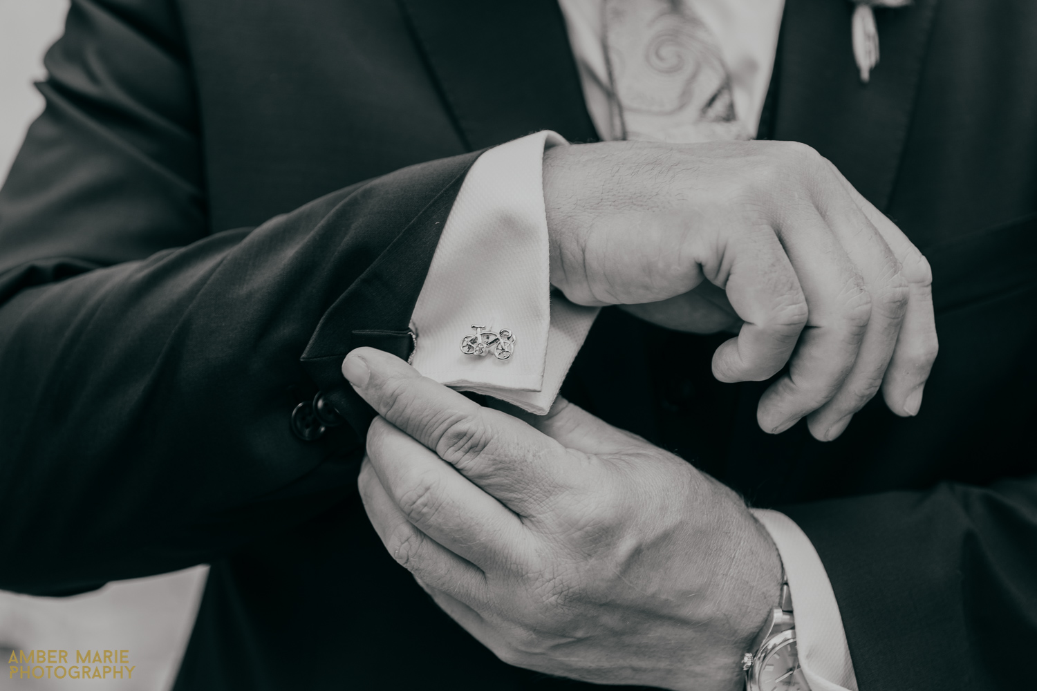 Close up black and white wedding photo of grooms cuff links