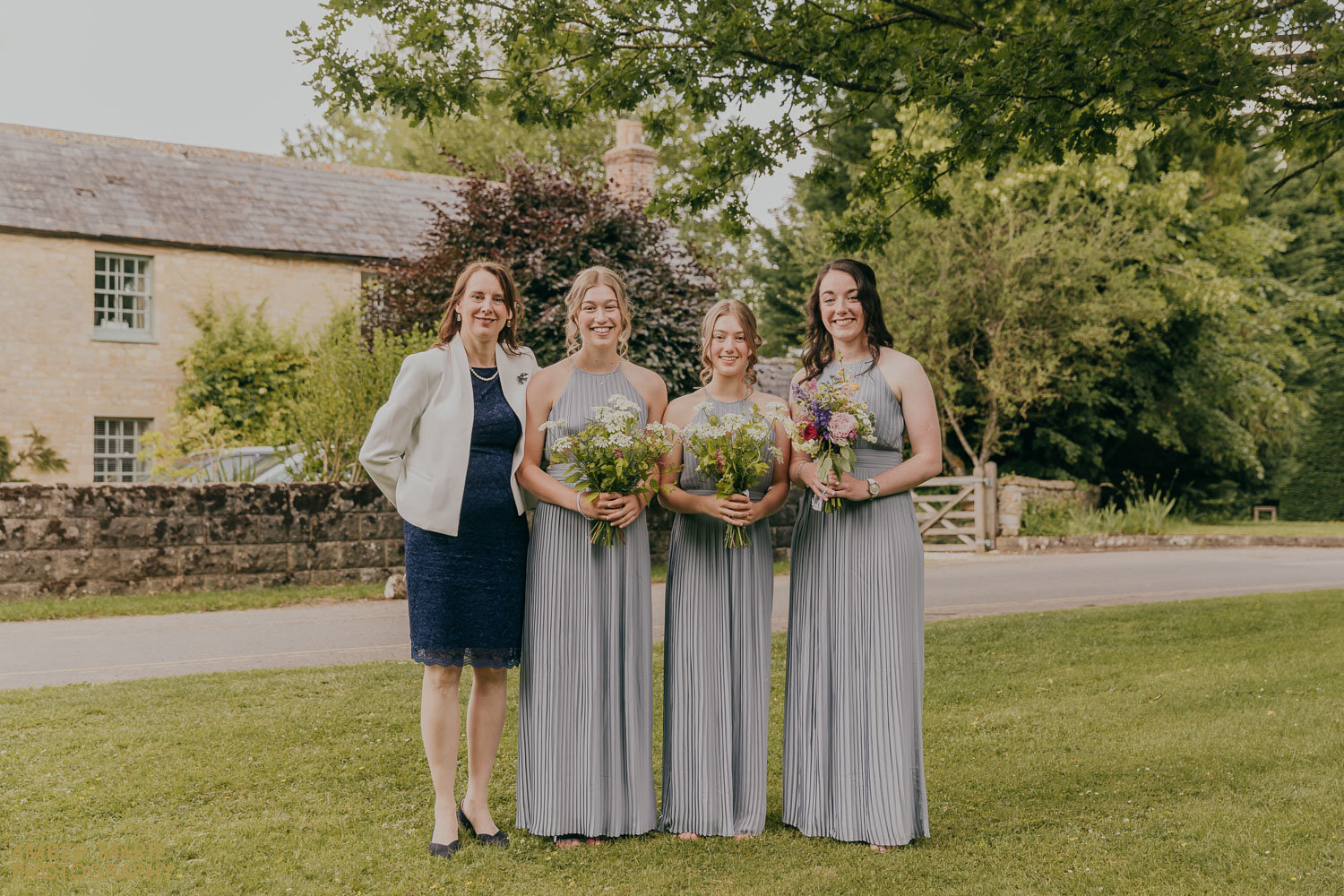 Relaxed group photo of bridesmaids outside Fairford Church wedding