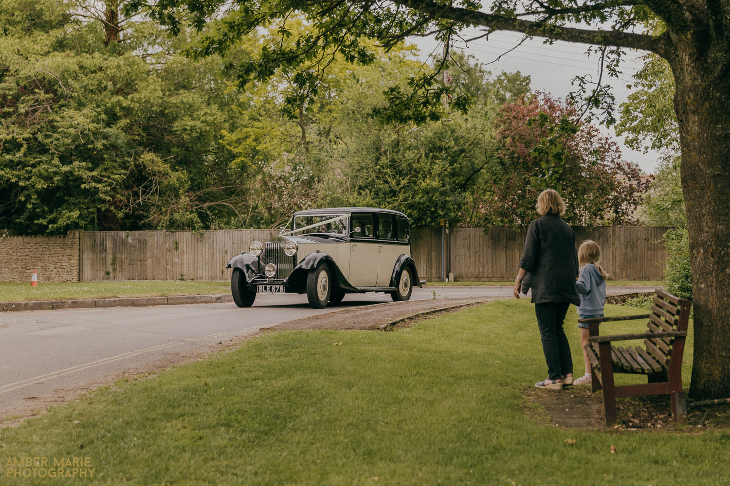 Documentary wedding photo of bride arriving at church in vintage car as neighbours watch