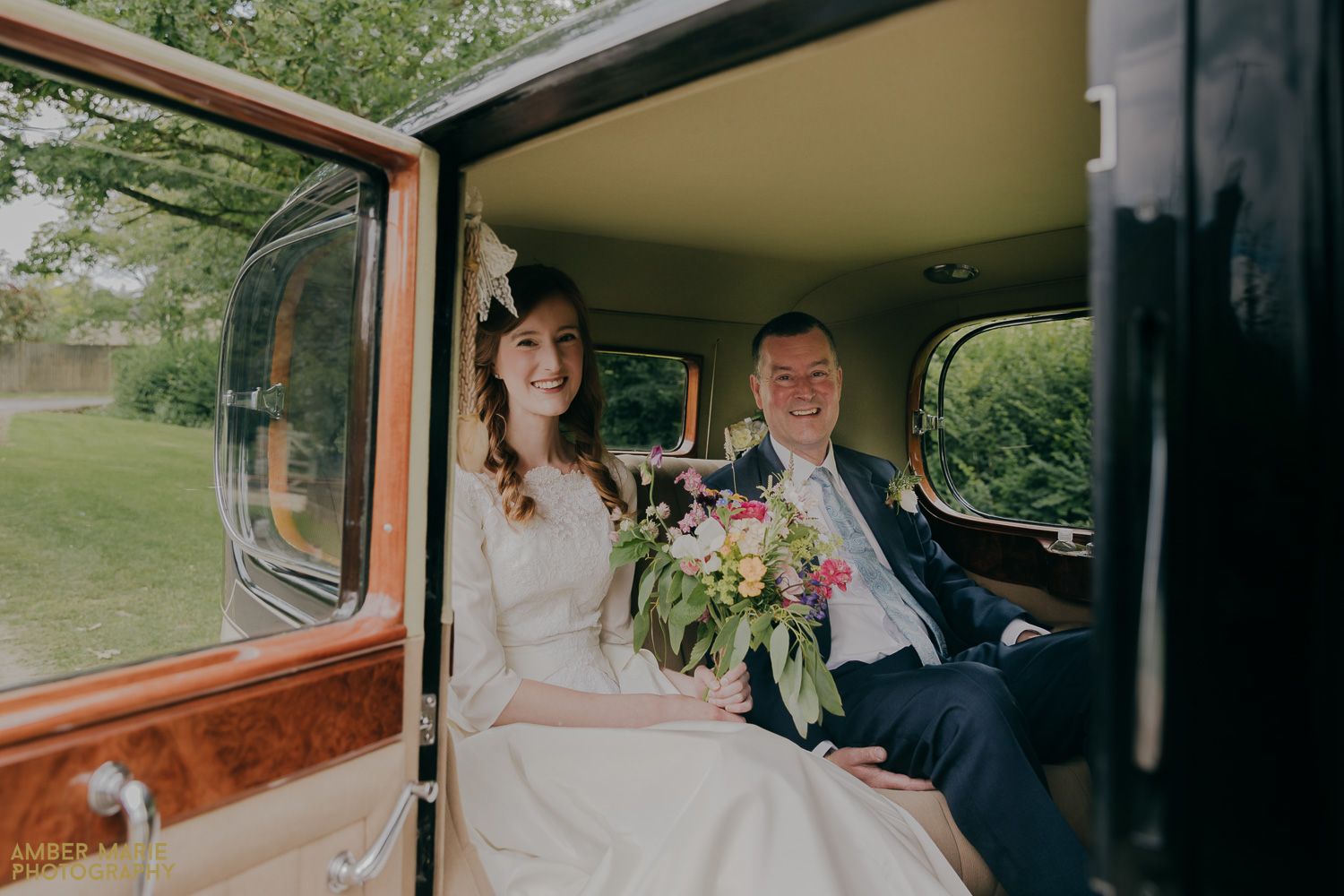 Bride and dad sat in back of vintage car outside church