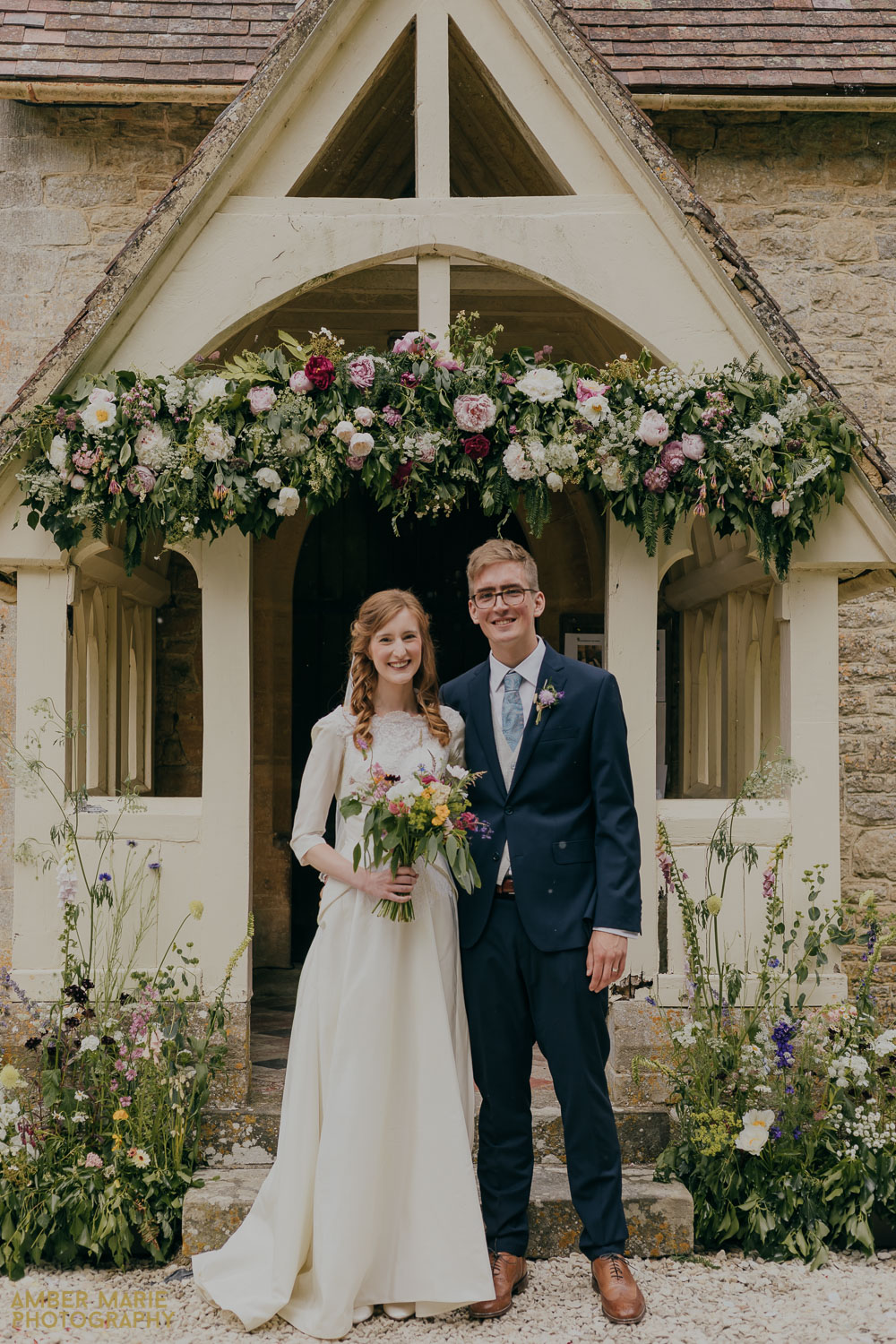 Vintage bride and groom outside Whelford Church in The Cotswolds