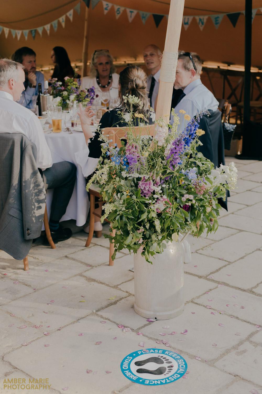 Rustic milk urn full of summer wedding flowers