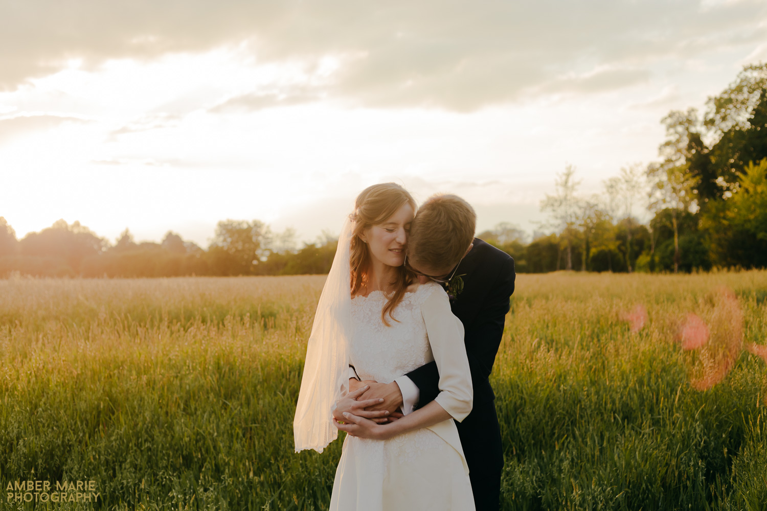 Natural portrait of bride and groom in a field at sunset