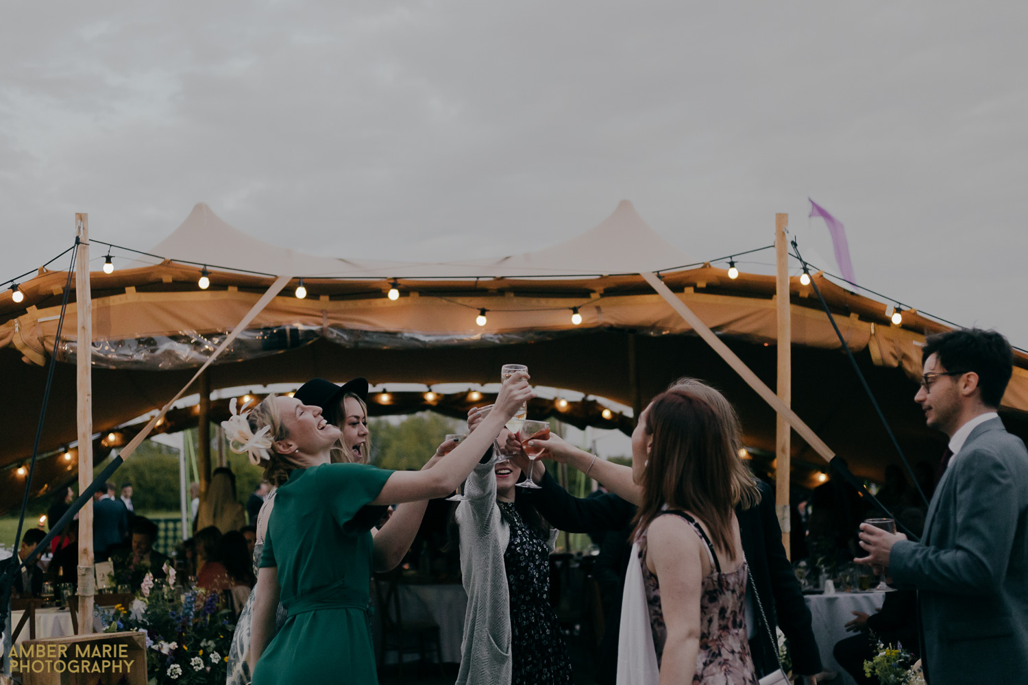 Joyful guests dancing at Bride and groom dancing in front of Tipi at Jenners Barn wedding
