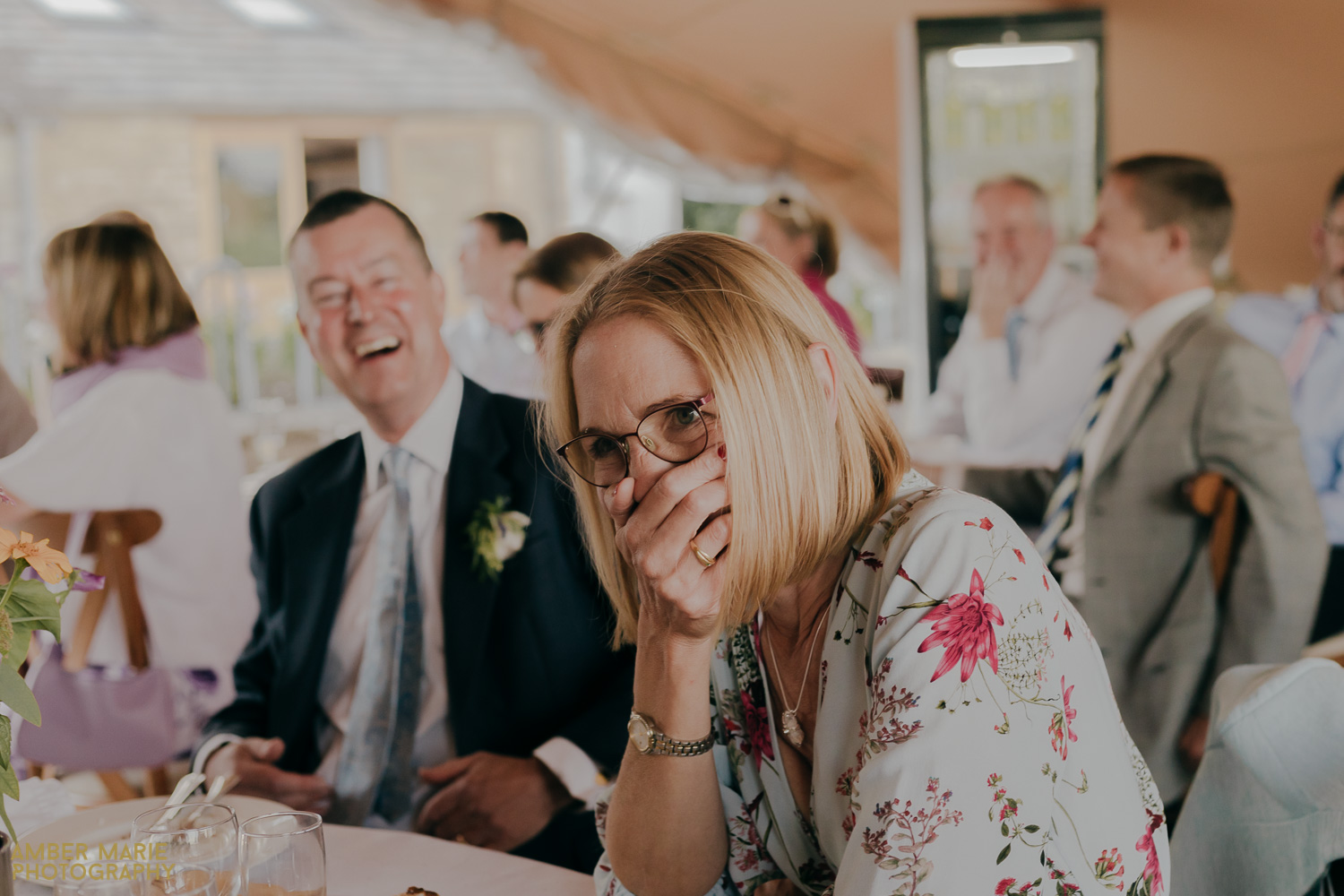 Natural photo of guest laughing during speeches at Bride and groom dancing in front of Tipi at Jenners Barn wedding