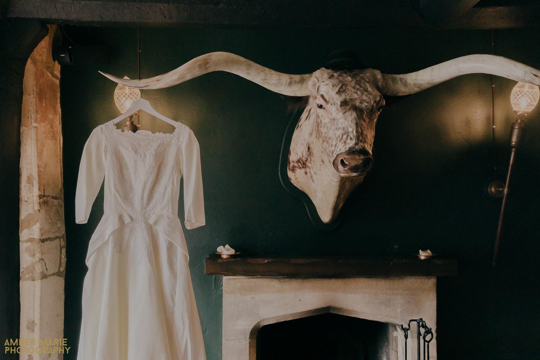 Vintage family heirloom wedding dress hanging off stuffed bull head