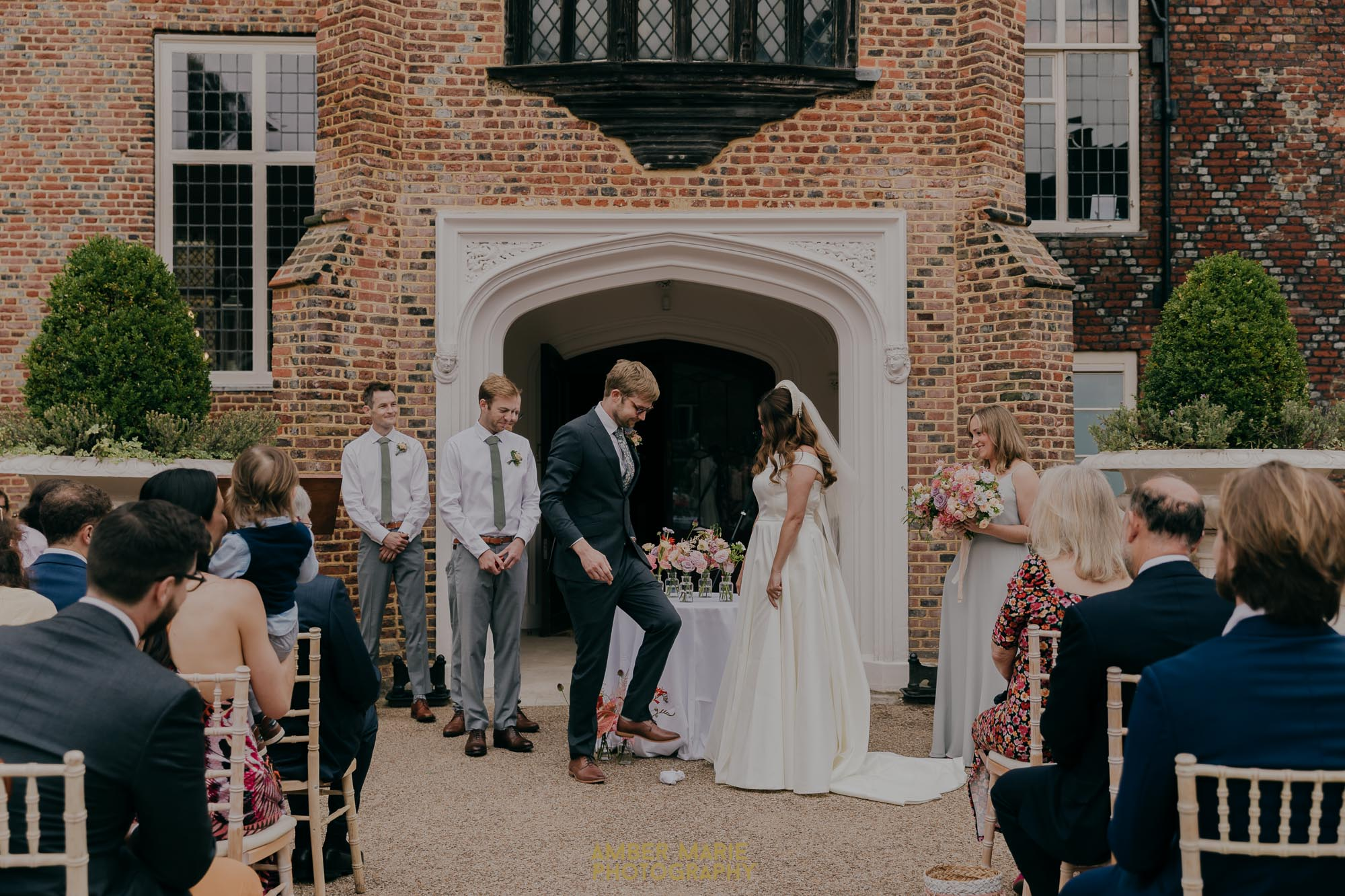 smashing the glass tradition during outdoor ceremony in Fulham Palace courtyard