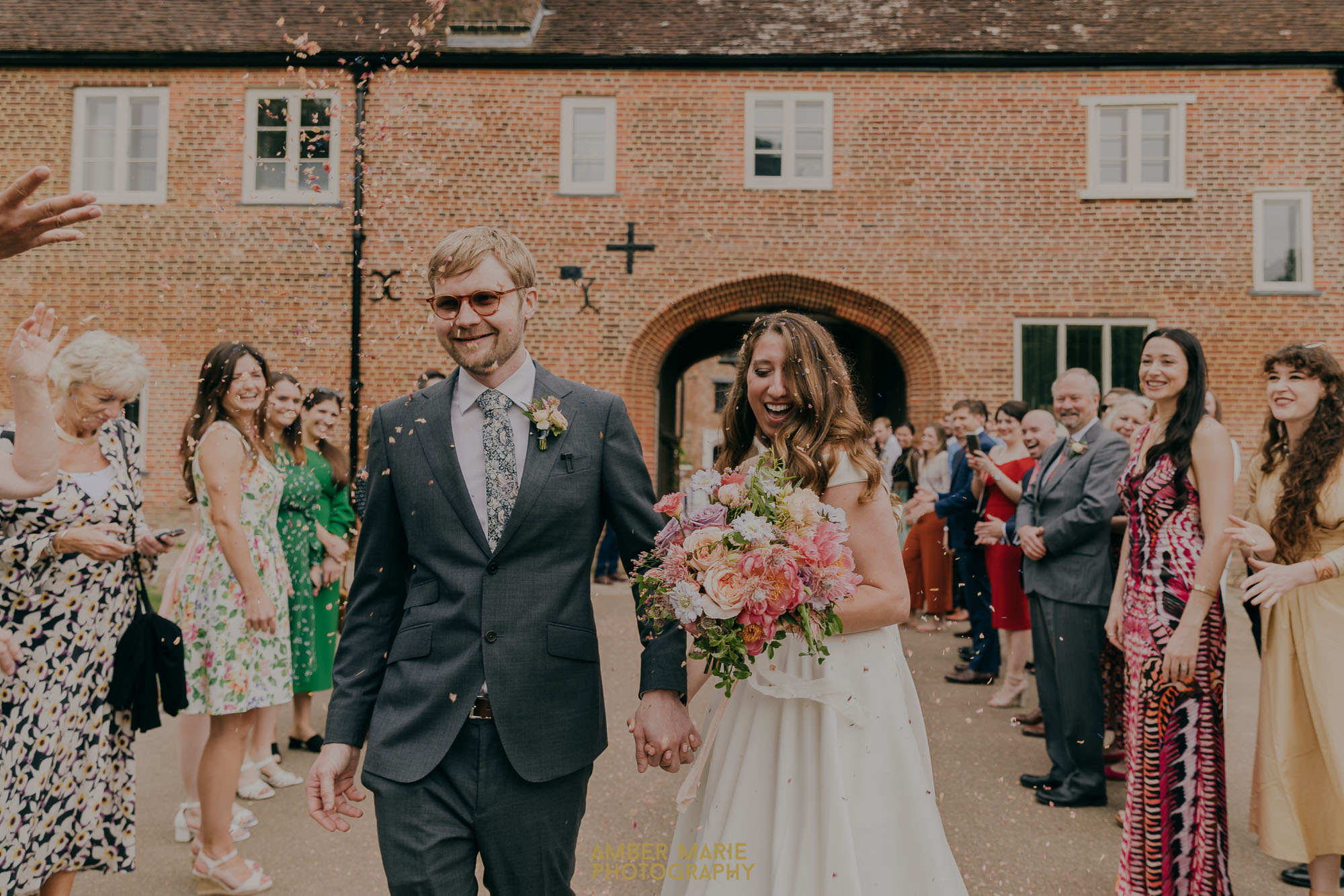 Joyful guests throw confetti on bride and groom at Fulham Palace wedding
