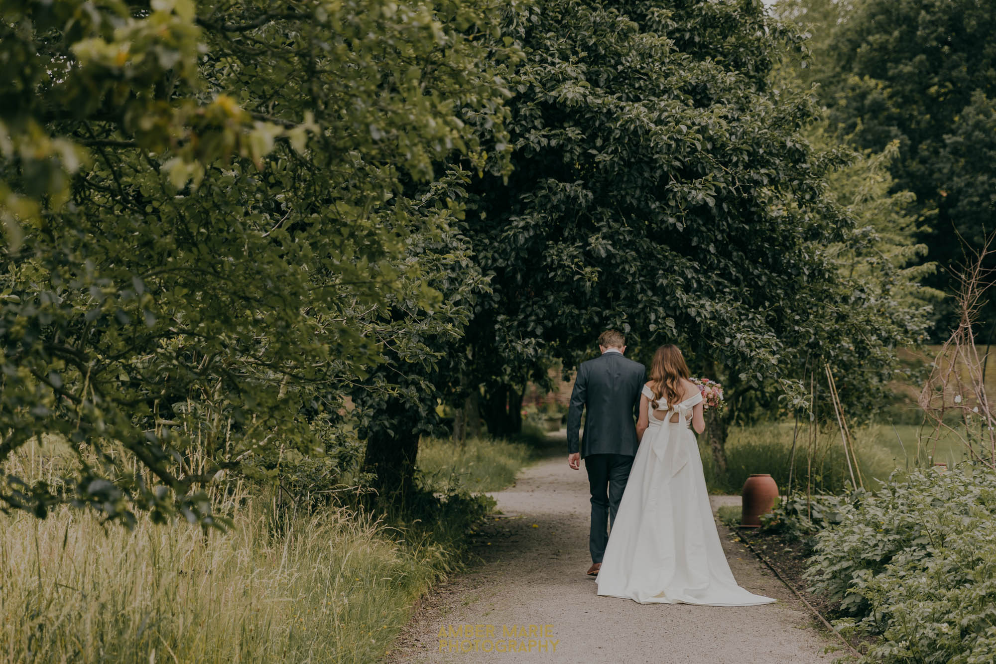 Bride and groom walking through walled garden at Fulham Palace wedding