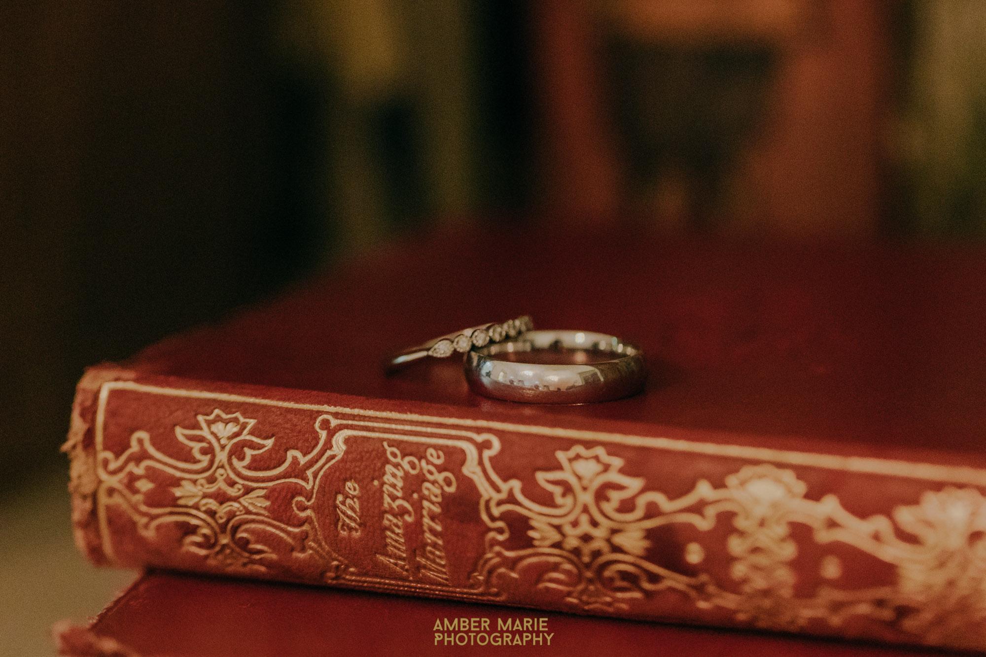 modern wedding photo of wedding rings on a classic hardback book 'the amazing marriage'