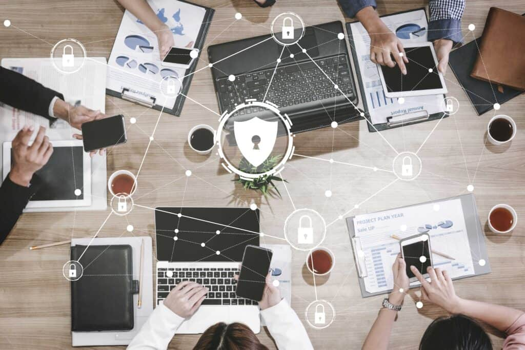 A bunch of electronic devices around a table with a overlay of a network displaying cyber security