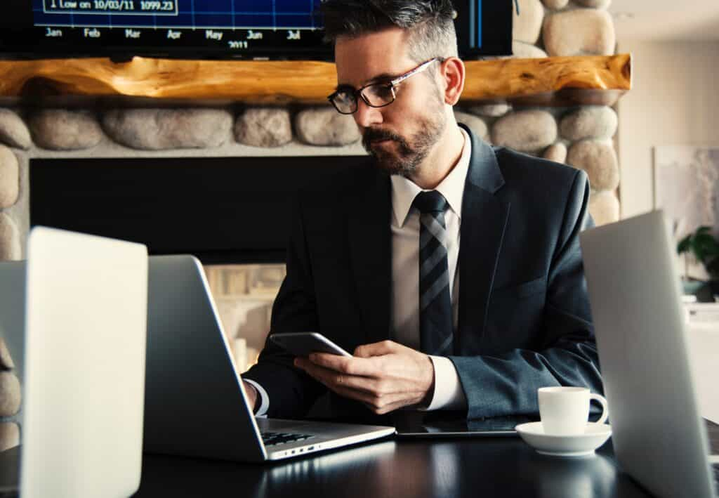 Business man using his company phone while also looking at his company computer