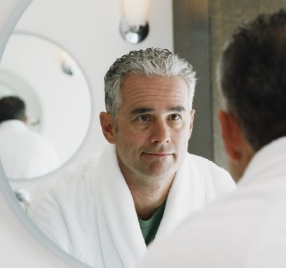 man looking into a mirror after receiving blue light therapy