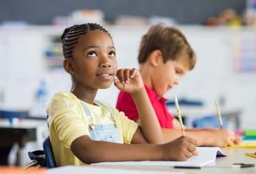 Middle-school girl in class thinking as boy is writing next to here