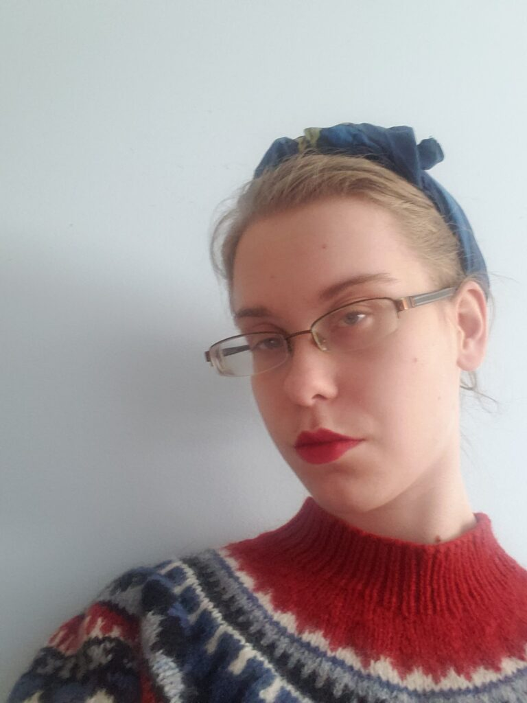 A photo of Grace, wearing a red and black sweater, red lipstick and glasses.