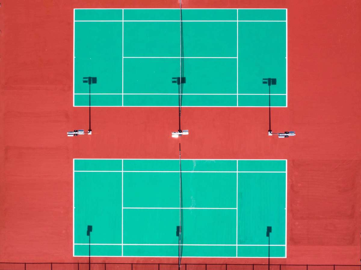 Green tennis court with red asphalt and turf