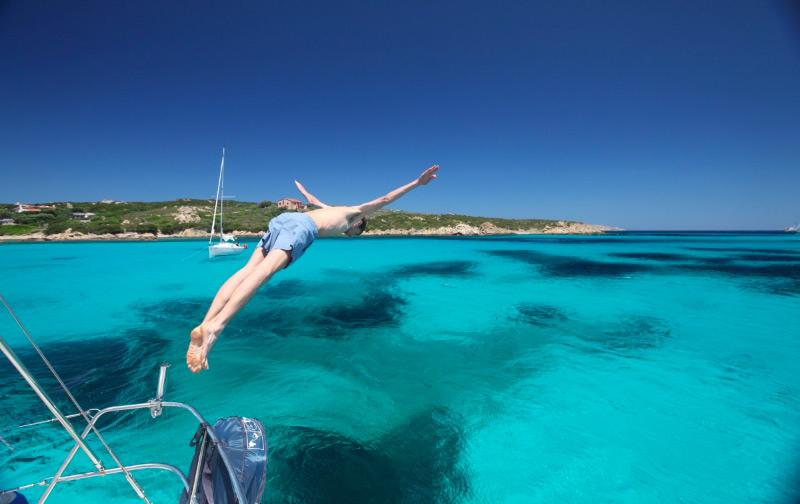 Jumping into the crystal clear waters of Cala Santa Maria, Sardinia, Italy