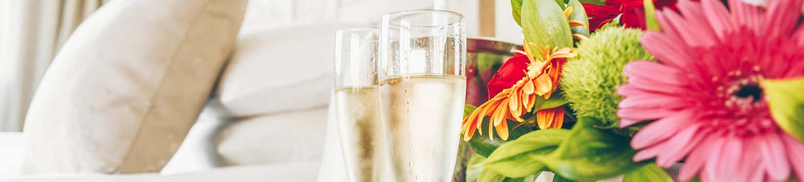 Two glasses of champagne in the upscale hotel room. Dating, romance, honeymoon, valentine, getaway concepts