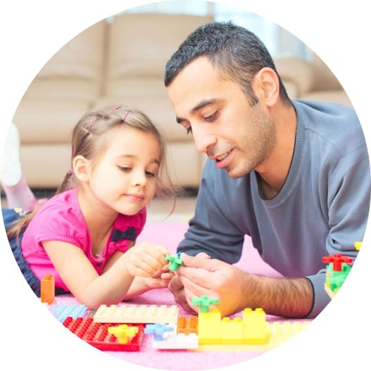 Dad and child playing with Legos for fine motor skills.