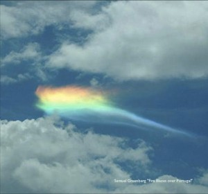 A photo of a rainbow shimmering behind a cloud