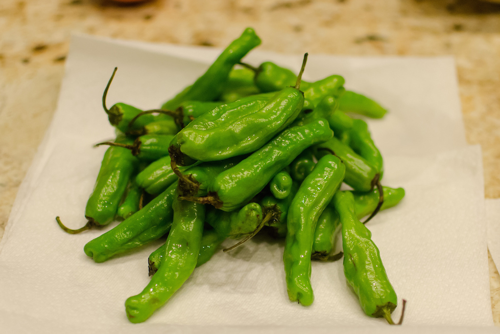 Look for shishito peppers at farm markets then take them home and saute them for serving.