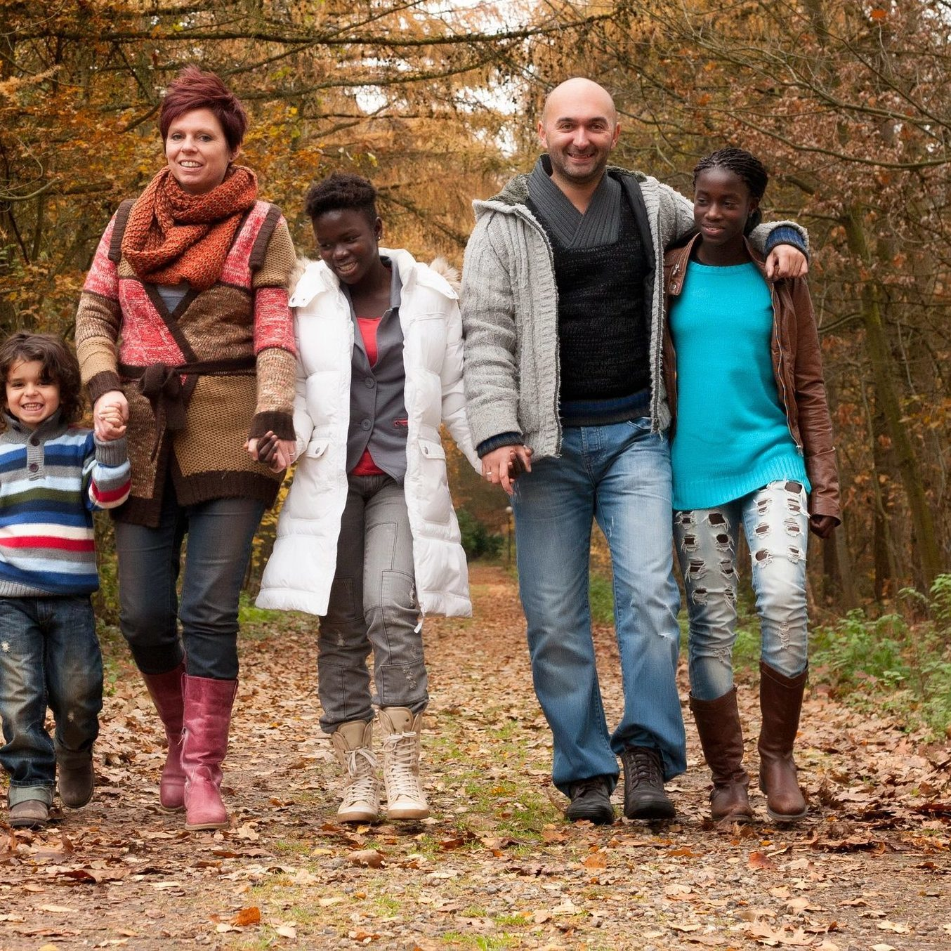 group of people walking on a wooded path