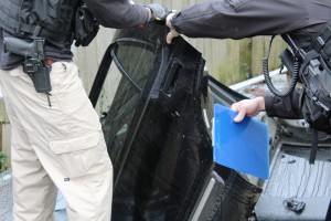 Detectives check vehicle ID numbers on a door