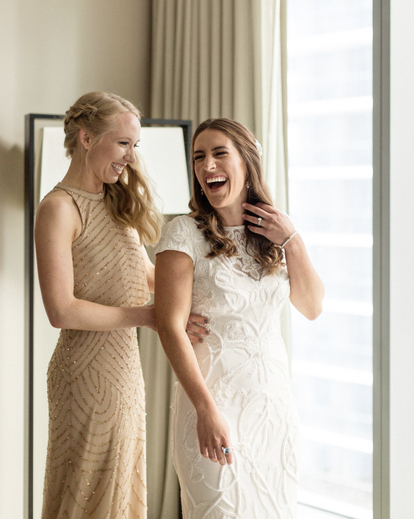 A unique Vizcaya Museum Wedding in Miami The Creatives Loft Weddings Miami bride and Maid of Honor laughing while dressing