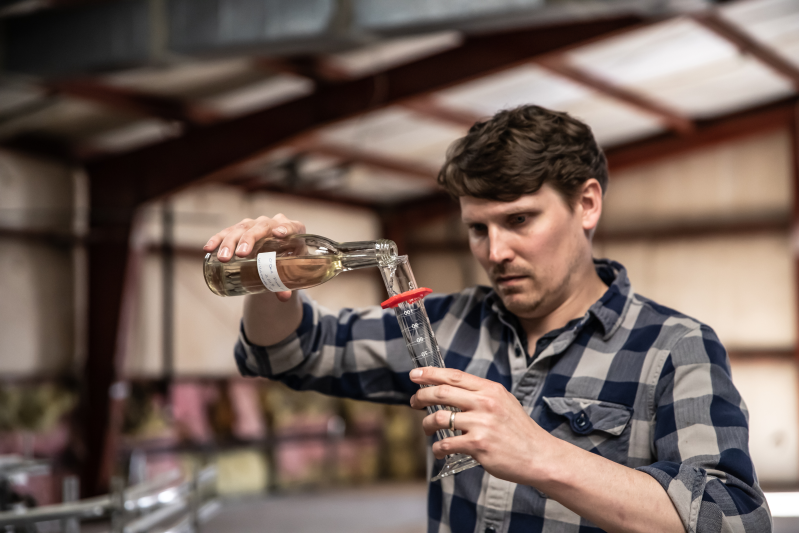 image of the head wine maker at the obc wine project evaluating the chemistry of winemaking