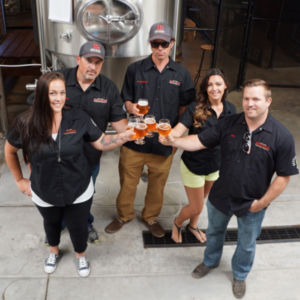 photo of the five company founders of revision brewing at the brewery in front of brewing mash ton