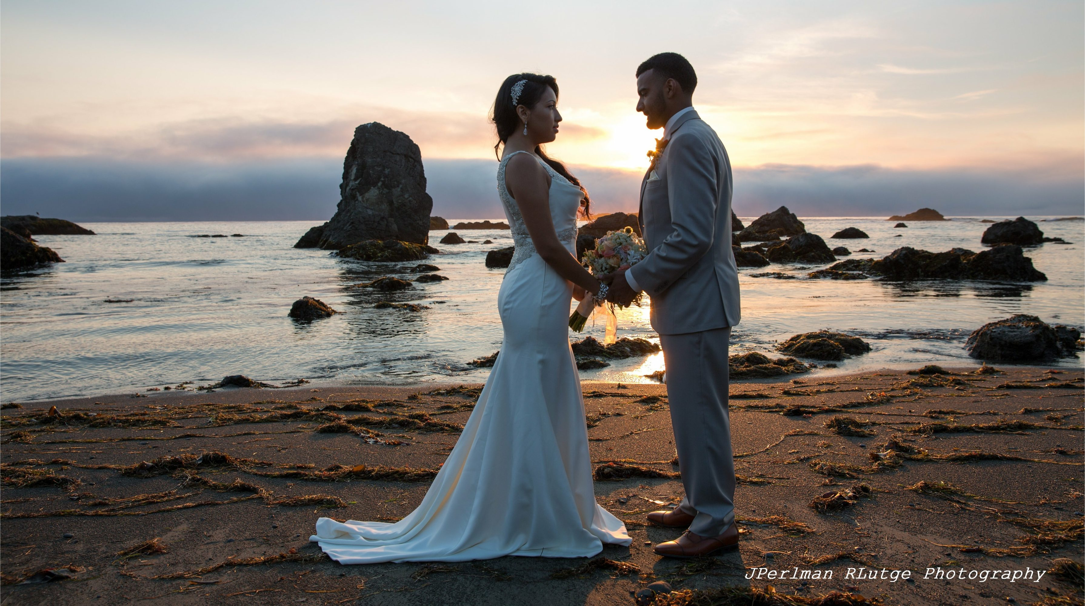 Johana and Isaac face each other, holding hands, on the beach at Westport, California, shortly after their wedding by Elope Mendocino.