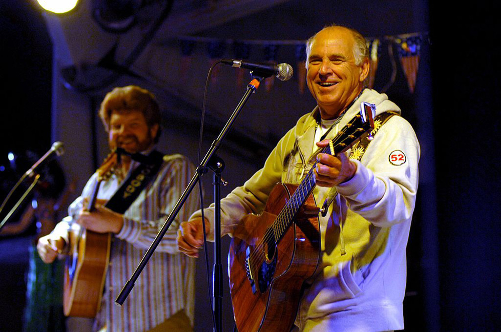 "Recording artists Jimmy Buffett, right, and Mac Macnally, a member of the ""Coral Reefer Band,"" perform a USO concert for the Sailors of the Nimitz-class aircraft carrier USS Harry S. Truman. Photographer U.S. Navy - Chief Mass Communication Specialist Michael W. Pendergrass / WikiCommons"