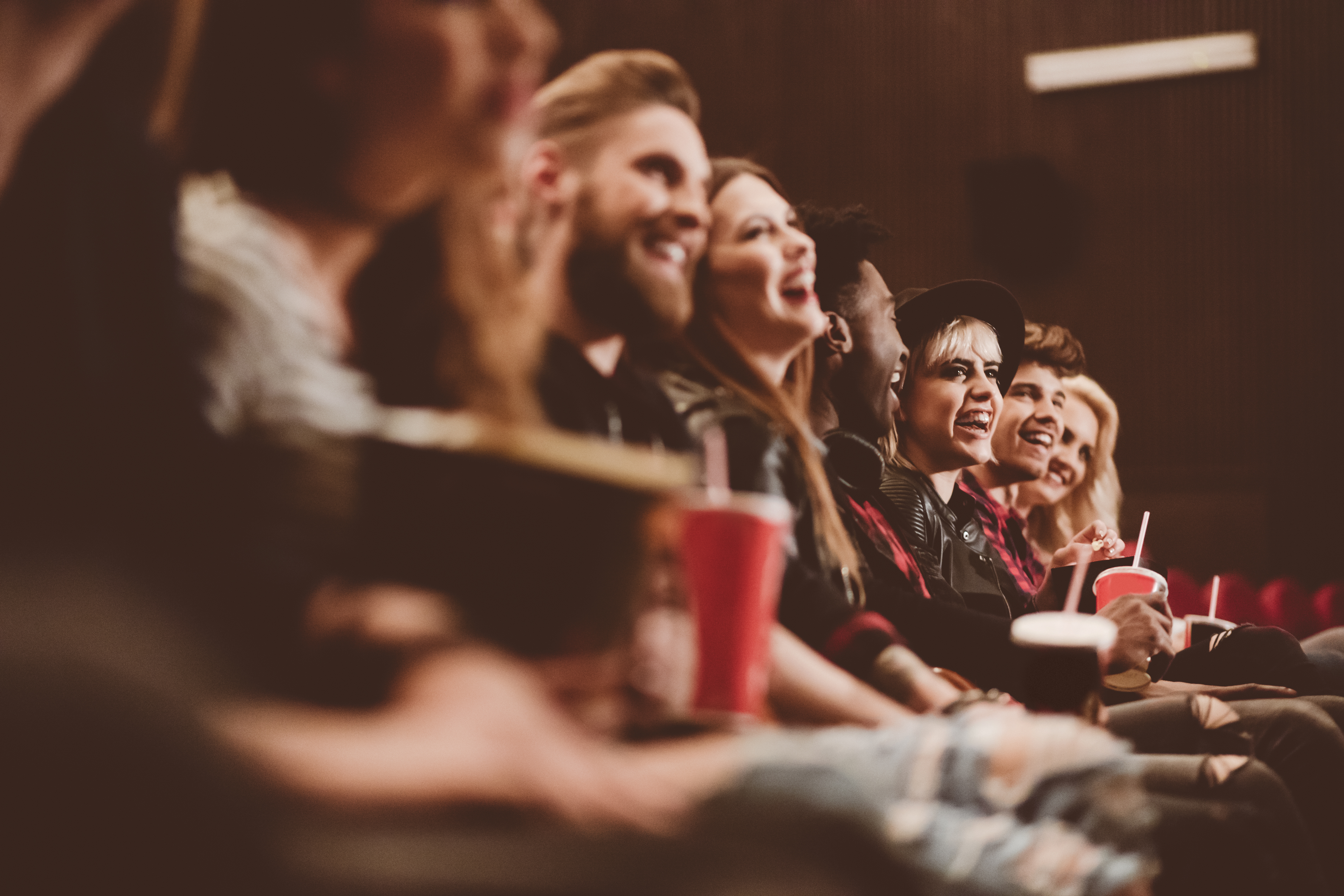 Group of people in the movie theater. Siede view, close up of hands, legs and drinks.