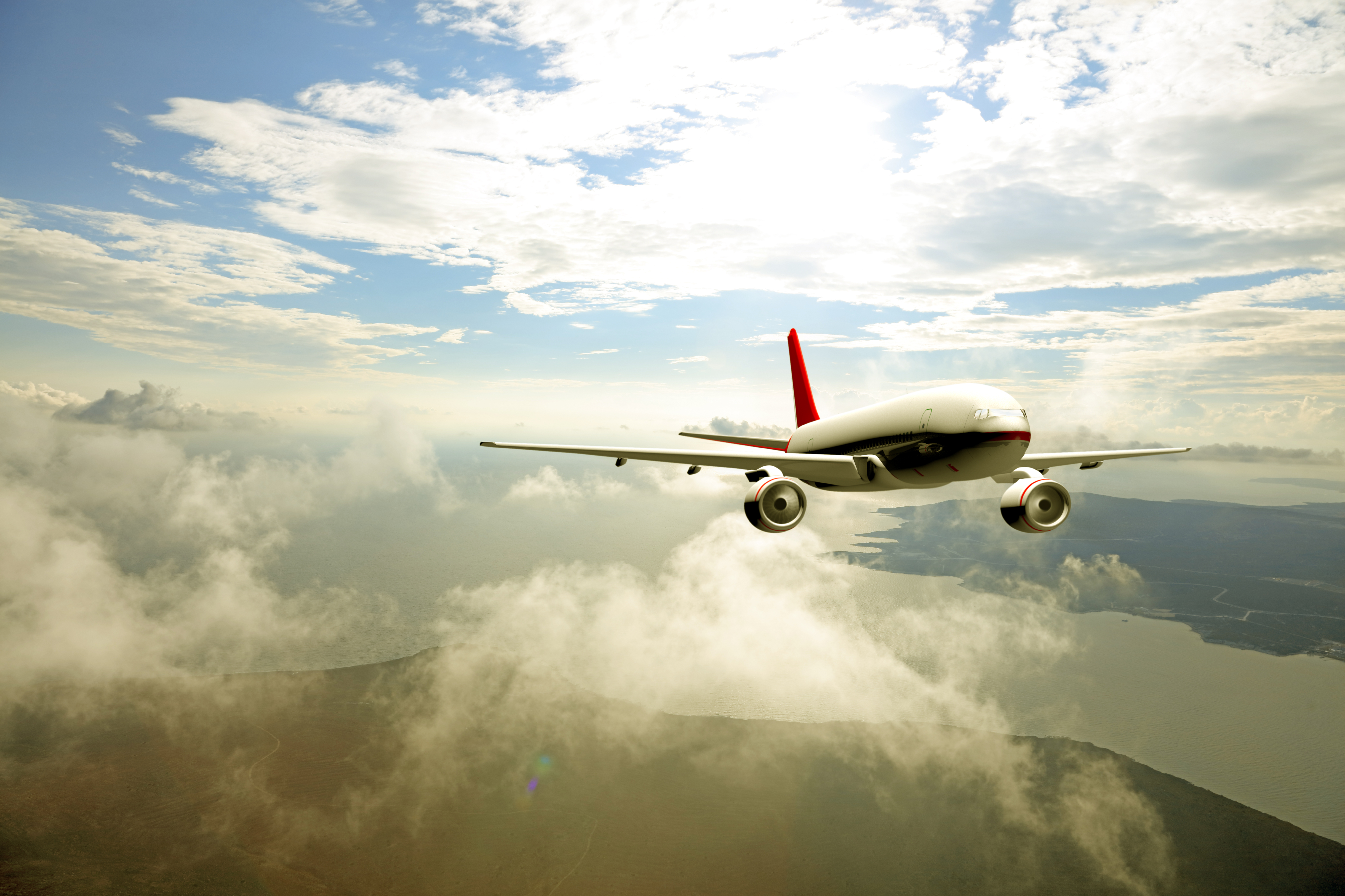 airplane flying above the above the puffy clouds with seascape