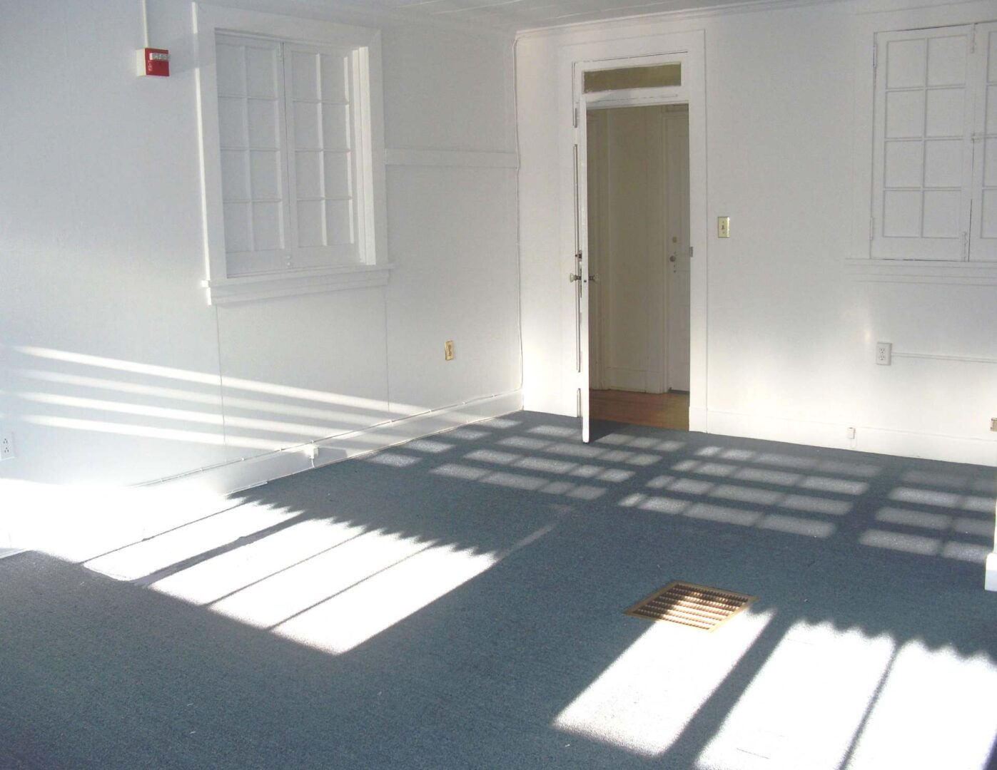 Large windows and deep blue carpet of a sunlit office at 222 Severn / W&P Nautical in the historic Trumpy Yacht building near Annapolis.