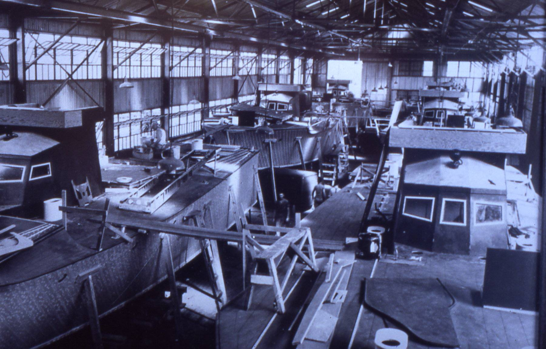 """Interior photo of """"The Big Shed"""" circa 1943 as six PT boats are being built for service in World War II at 222 Severn / The Yard."""