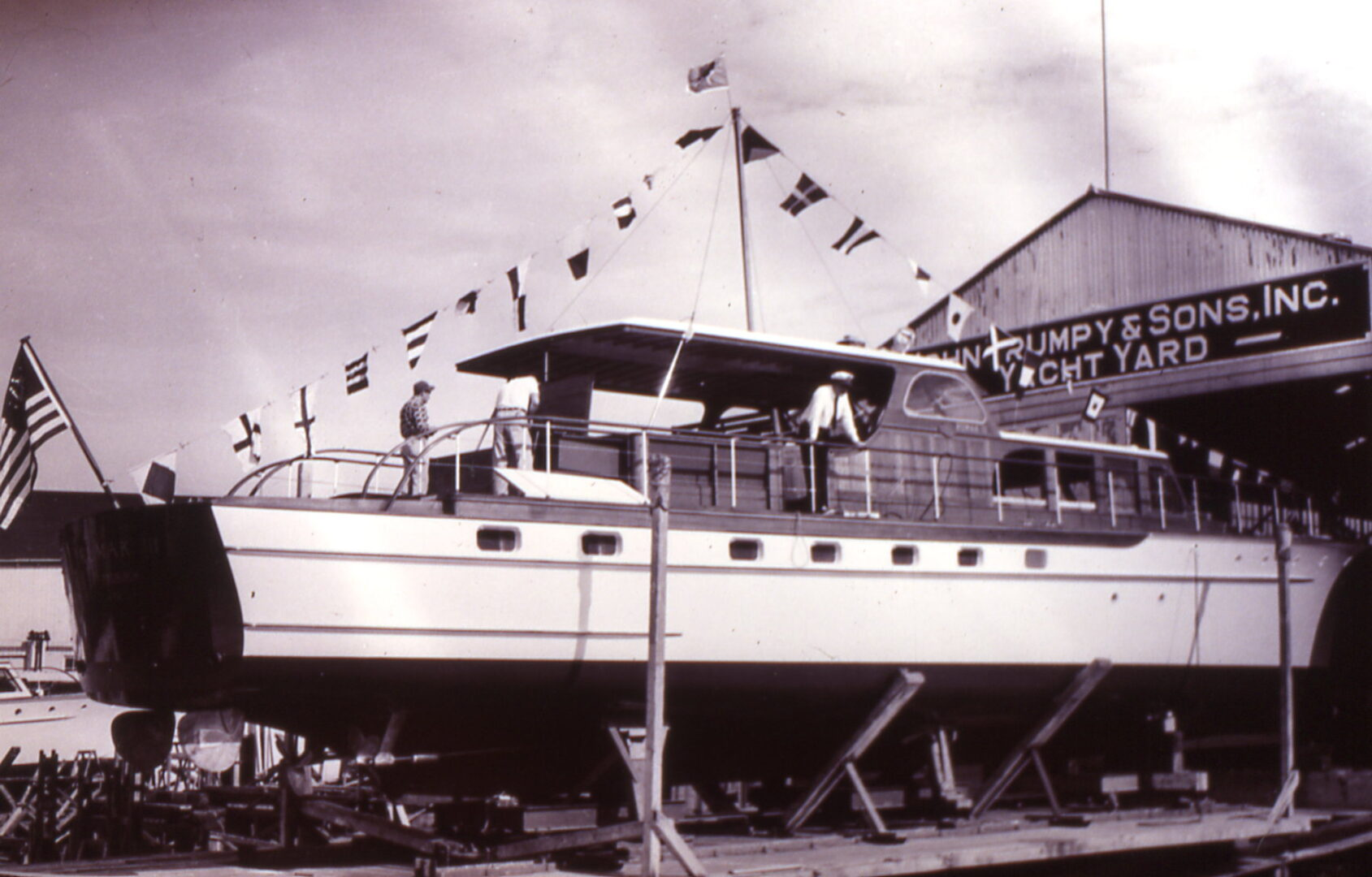 Circa 1950, a classic Trumpy yacht is launched into Spa Creek amid fanfare and flags, across from downtown historic Annapolis.