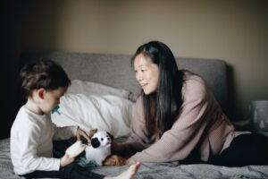 mother and child playing with white and black dog plush toy