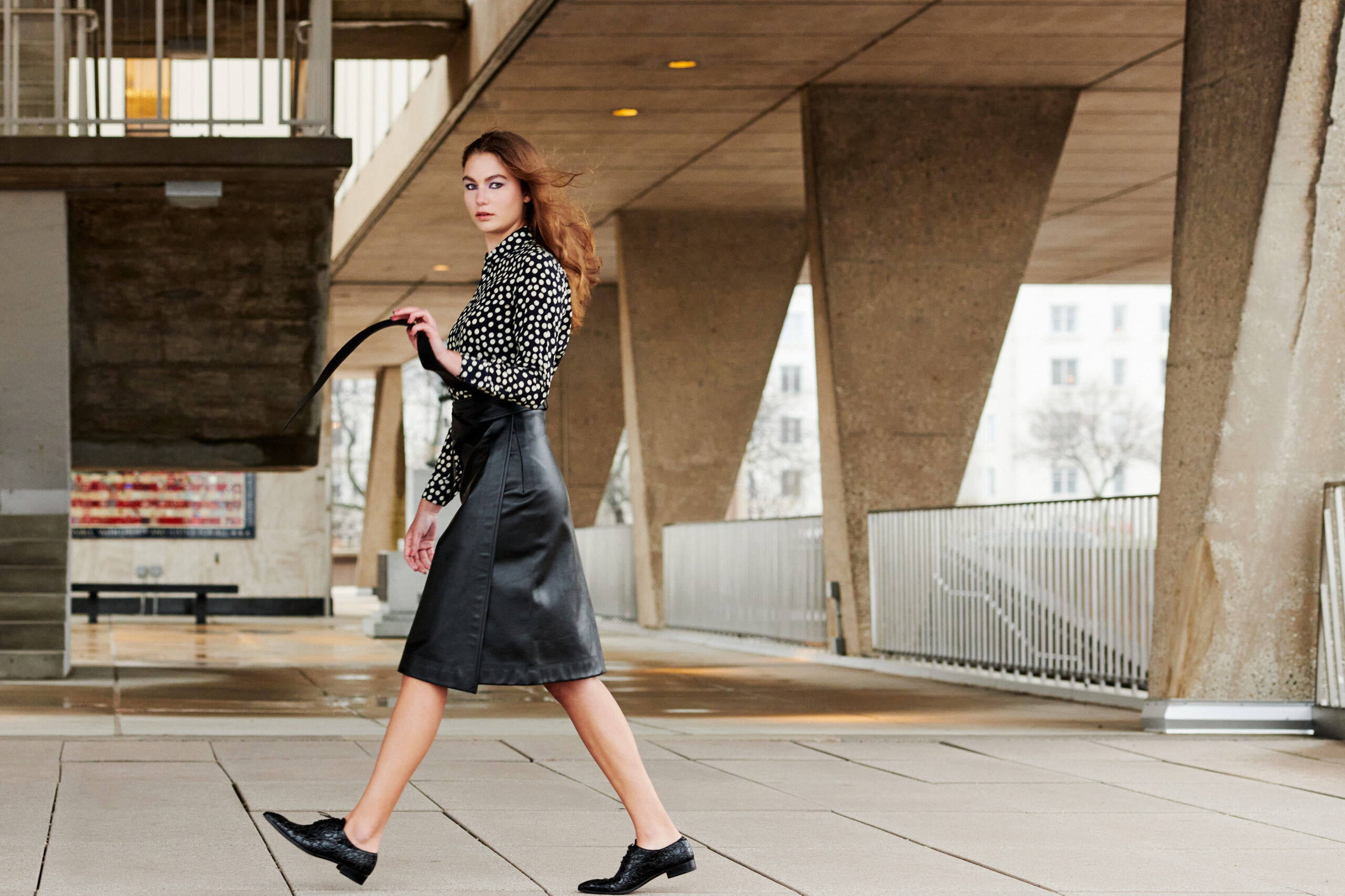 Kate wears SAINT LAURENT dotted silk blouse and BALENCIAGA leather belted skirt.