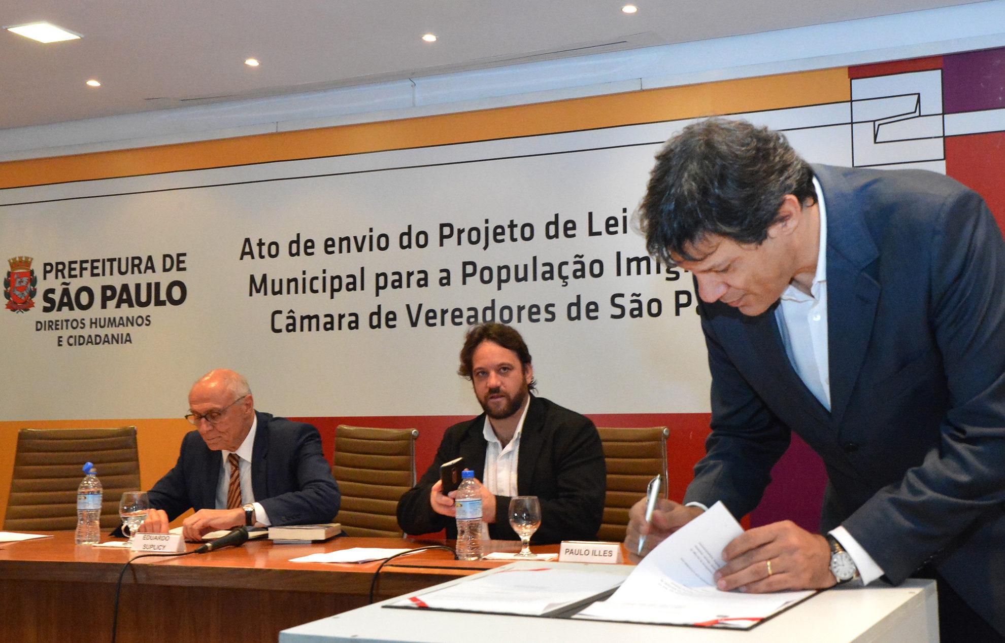 Haddad (d) assina projeto lei que cria política para imigrantes, acompanhado por Paulo Illes (c) e Suplicy (e). Crédito: Fernando Pereira/SECOM