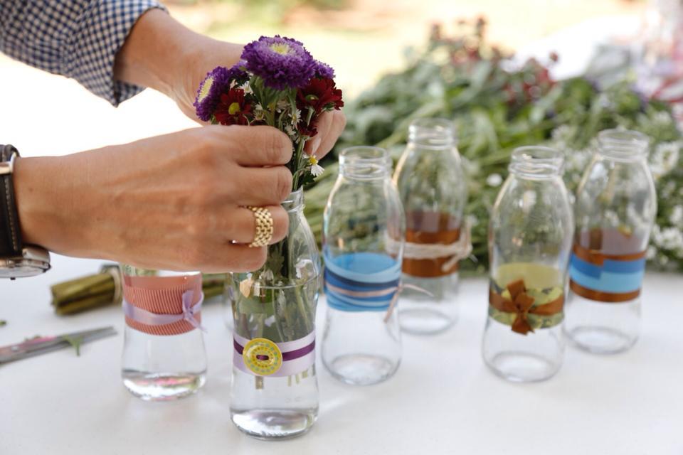 Com pequenas garrafas de vidro e flores, os arranjos do Flores para os Refugiados ganham forma. Crédito: Divulgação