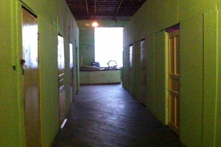 Interior de um edifício ocupado. A grande antiga sala de entrada foi transformada em quartos pequenos, instalando paredes de madeira compensada. Crédito: Heike Drotbohm