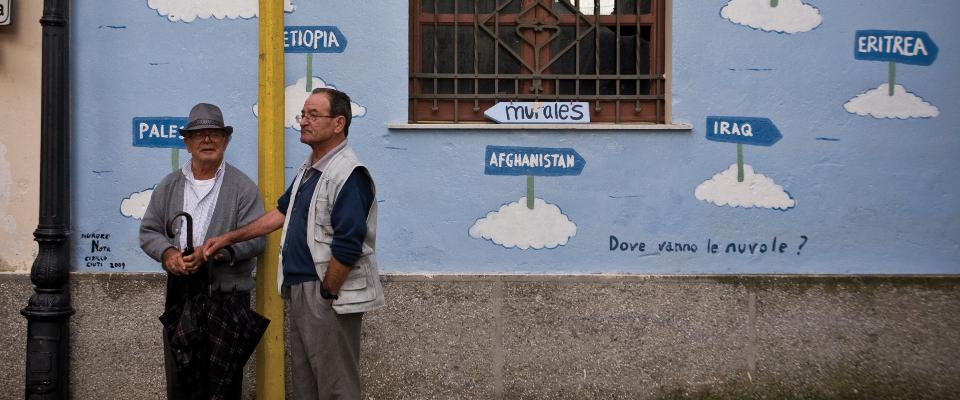 """""""Onde vão as nuvens"""", questiona mural na cidade de Riace, no sul da Itália. Cada nuvem tem o nome de um país. Crédito: Reprodução/www.riaceinfestival.it"""