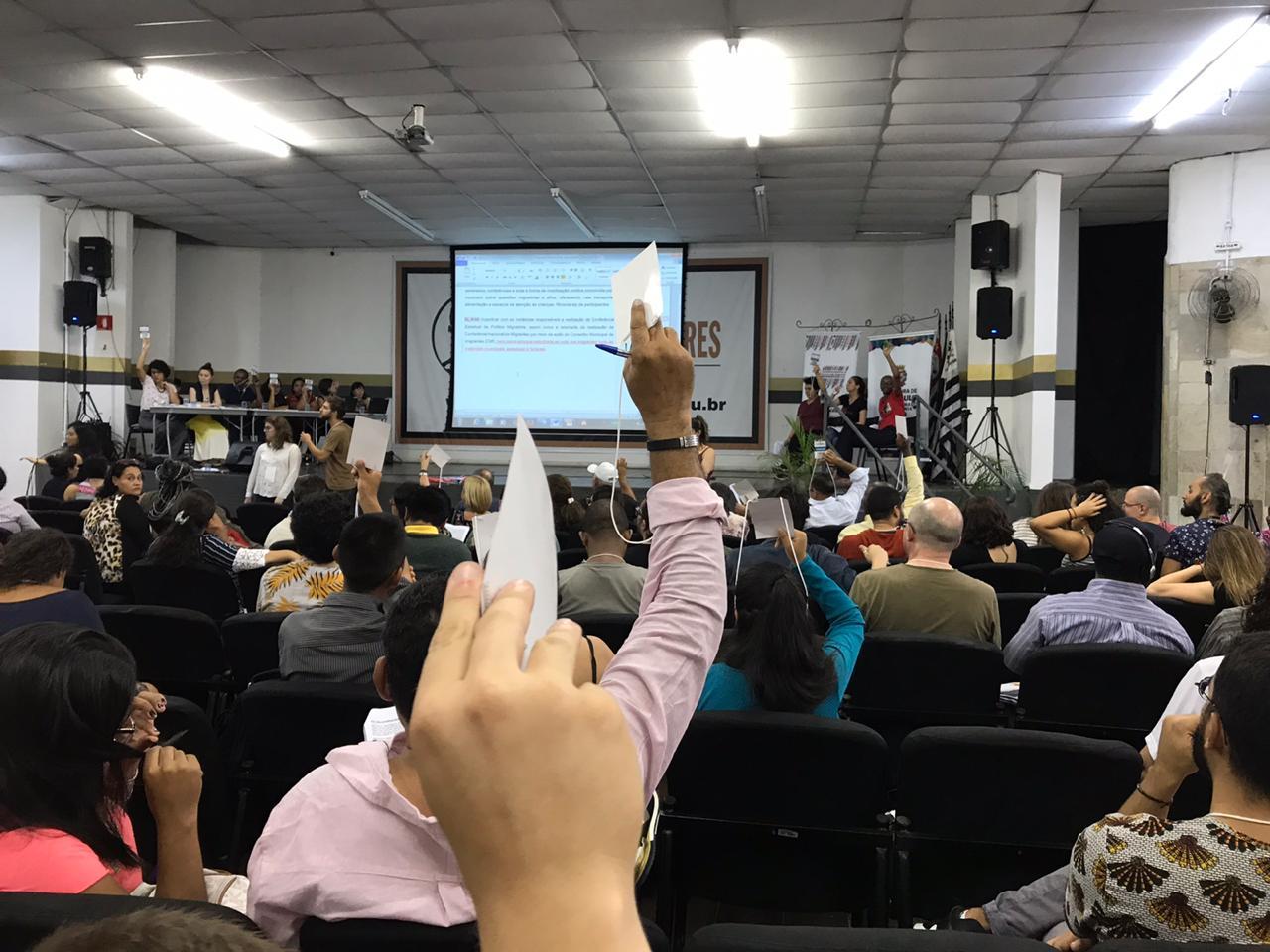 Delegados imigrantes votam durante plenária final da 2ª Conferência Municipal de Políticas para Imigrantes, em São Paulo