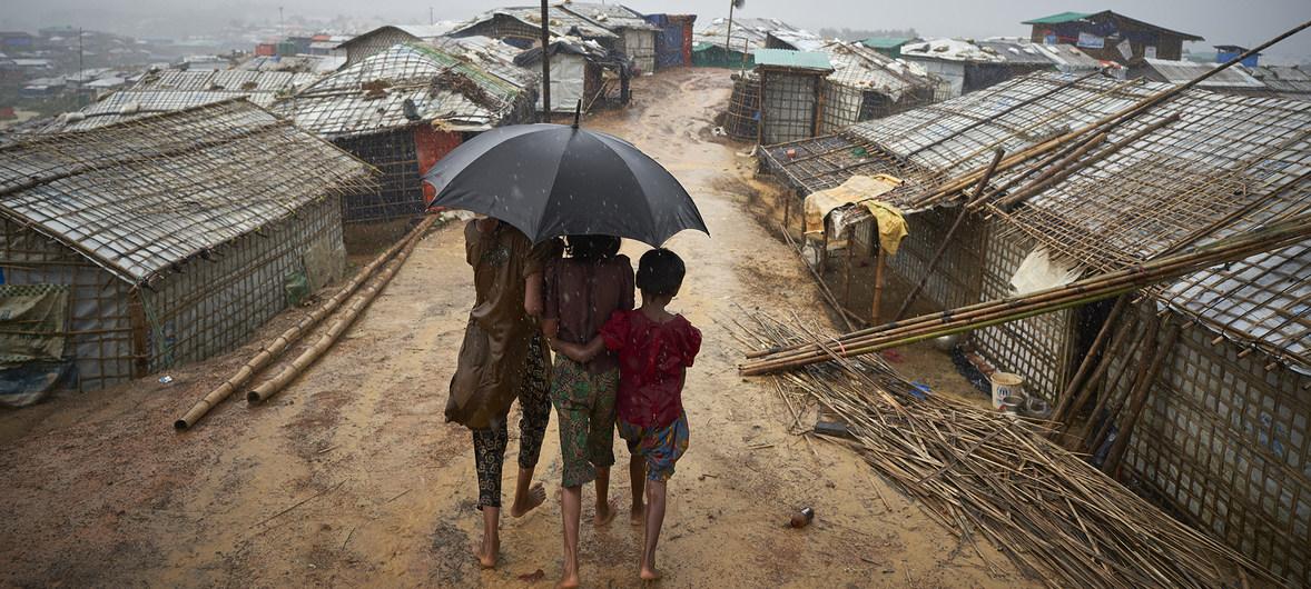 Refugiados rohingya caminham por uma trilha durante uma forte chuva de monções no campo de refugiados de Kutupalong, no distrito de Cox's Bazar, em Bangladesh. Crédito: David Azia/ACNUR