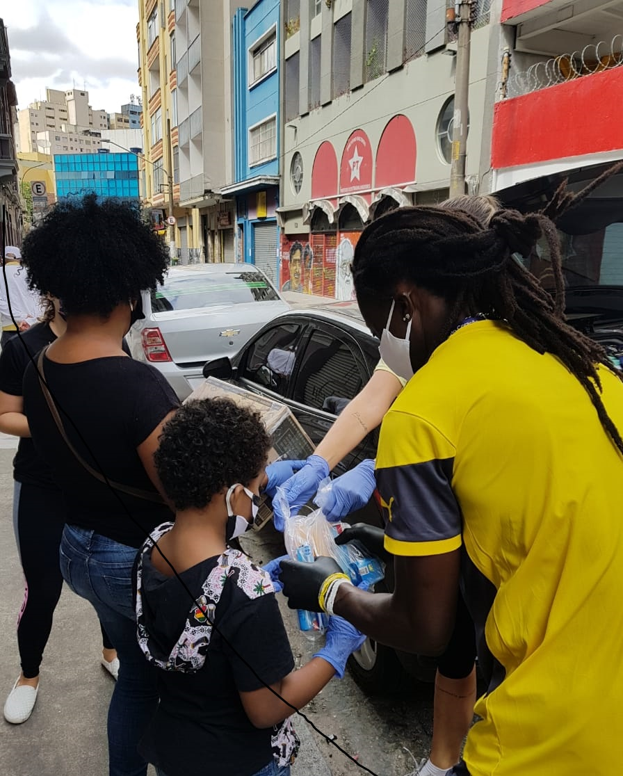 Integrantes das ONGs África do Coração e Grupo Amar distribuem cestas básicas no centro de São Paulo