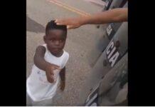 Criança haitiana estende a mão para policiais durante protesto na fronteira entre Brasil e Peru, no estado do Acre