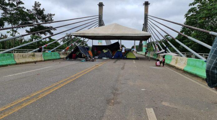 Imigrantes na ponte que liga Assis Brasil a Iñapari, no lado peruano